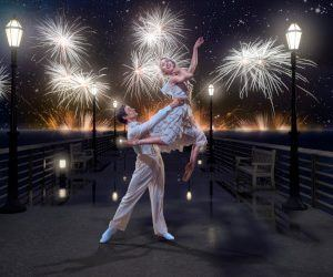 A couple in 1920s dress on a bridge, the man lifting the woman towards the sky lit by multiple white fireworks
