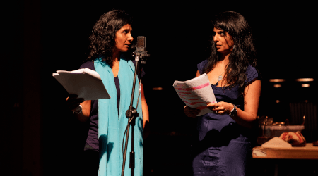 Two women stand by a microphone looking at each other and holding a script.