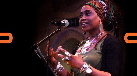 Khadijah Ibrahiim, a black woman wearing a striped head covering speaking at a microphone