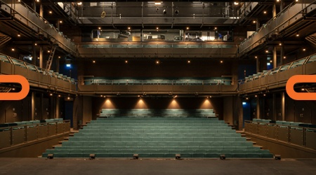 The empty Courtyard theatre with warm lighting and teal coloured seats