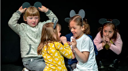 Two young children wearing paper mouse ears play together