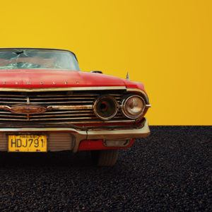 Image of a car on a mustard background. The car is red and shows signs of damage including a gunshot in the windscreen