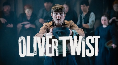 Actor Brooklyn Melvin as Oliver Twist standing looking plaintively at the camera with their hat in their hands as if asking for more