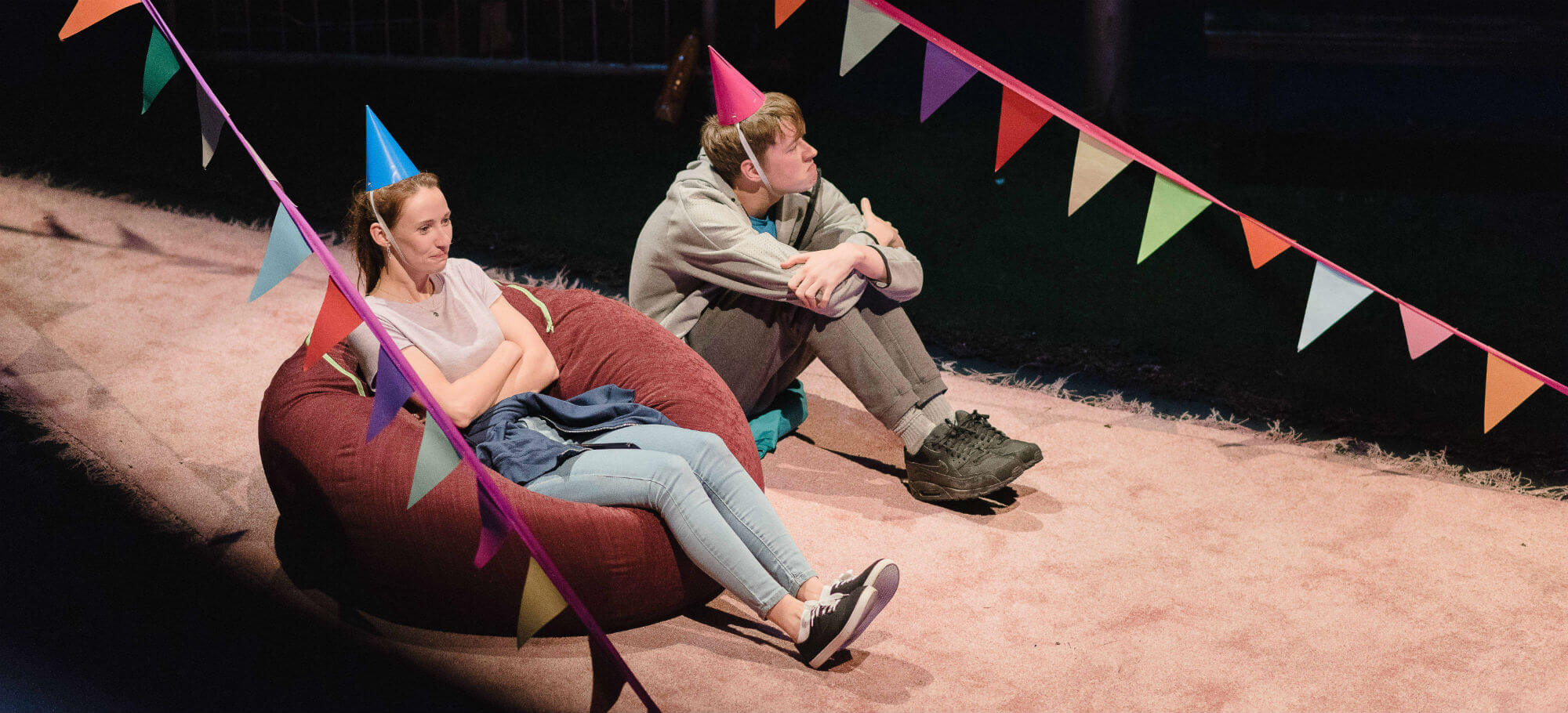 Two teenagers are sitting, one on a bean bag, one on the floor., between two garlands of colourful bunting. They are both wearing party hats and looking glum.